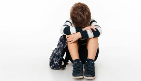 Menino triste tapando o rosto - automutilação na infância e adolescência