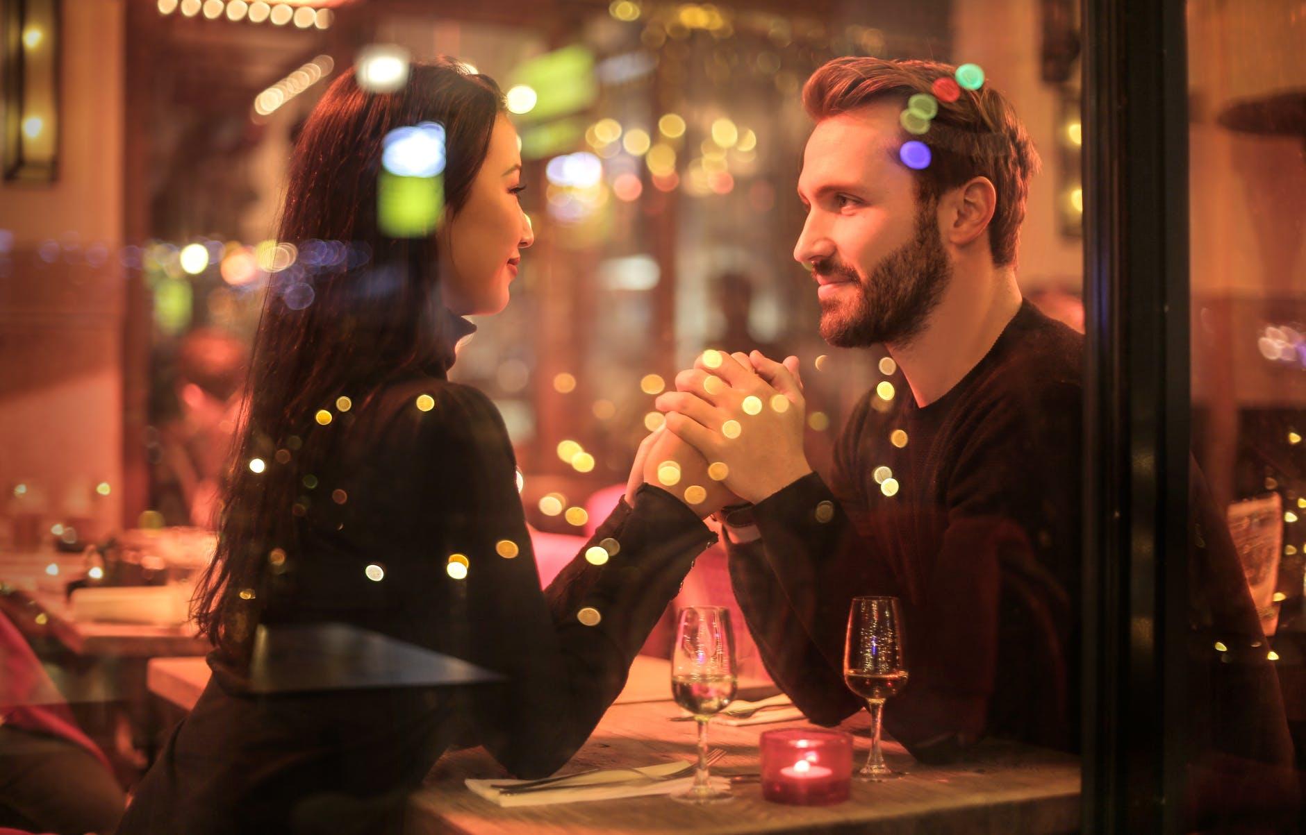 casal sentado de frente um para o outro dentro de um restaurante segurando as mãos enquanto se olham