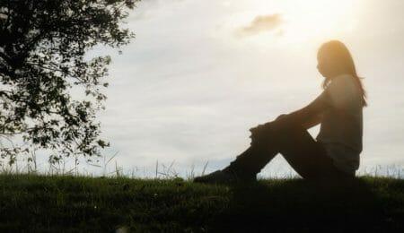 mulher sentada em parque com depressão