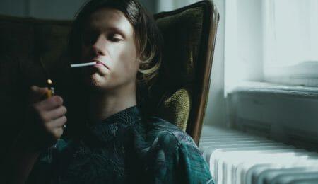 Homem com semblante triste acendendo um cigarro
