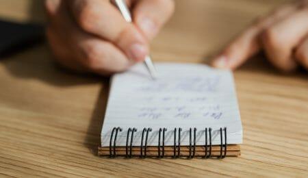 pessoa organizando suas tarefas em bloco de anotações, autossabotagem